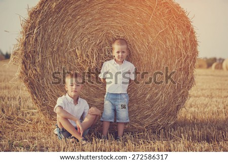 Two little brothers sitting near a haystack in wheat field on warm and sunny day, toned image - stock photo