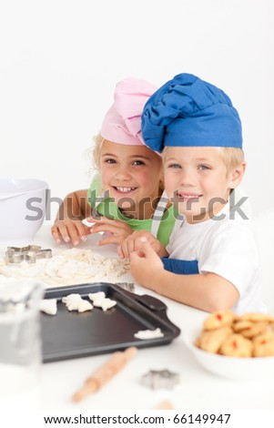 Two little chefs preparing cookies in the kitchen and smiling at the camera - stock photo