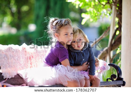 two little child sisters hug each other at sunny day in a beautiful park - stock photo