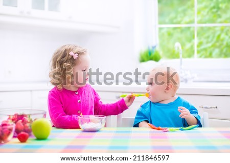 Two little children, adorable toddler girl and funny baby boy, eating yoghurt with berry and fruit together, sister feeding the brother, having healthy breakfast in a white sunny kitchen with window - stock photo
