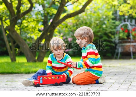 Two little children in colorful clothing with stripes playing with red school bus and toys in summer garden on warm sunny day. Learning to play and communicate together. - stock photo