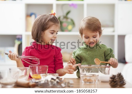 Two little children making cookies. - stock photo