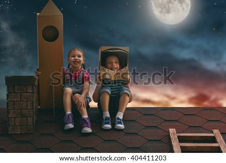 Two little children playing astronauts. Child boy in an astronaut costume and child girl with toy rocket standing on the roof of the house and looking at the sky and dreaming of becoming a spacemen. - stock photo