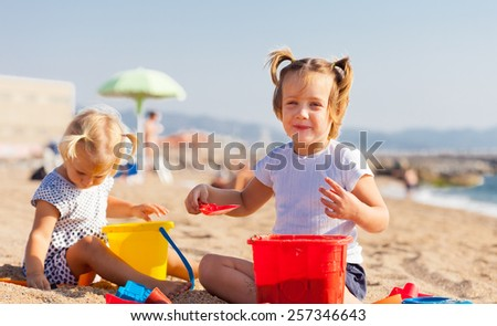 Two little children sitting on beach - stock photo