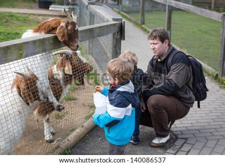 Two little cute boys and young father feeding animals in zoo - stock photo