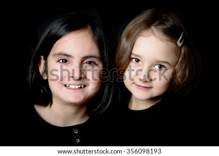 Two little cute girls dressed in black posing on a black background - stock photo