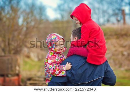 Two little cute girls hugging their father on a sunny spring day. Happy family. - stock photo