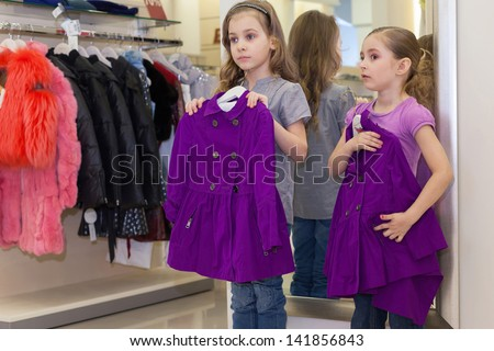 Two Cute Clothing Store Two little cute girls near a