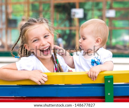 Two little cute sisters with the park - stock photo