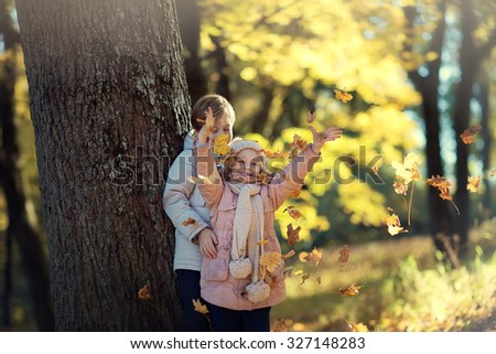 Two little cute smiling kids in warm jackets walking together in a park on a sunny autumn day. Friendship between siblings. Happy family concept - stock photo