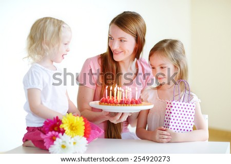 Two little daughters wishing their mother a happy birthday - stock photo