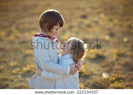 Two little embracing children in the field on a cool summer day. Happy family. - stock photo