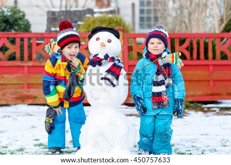 Two little fiends, kid boys making a snowman, playing and having fun with snow, outdoors  on cold day. Active outdoors leisure with children in winter. - stock photo