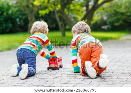 Two little friends boys in colorful clothing with stripes playing with red school bus toy in summer garden on warm sunny day. Learning to play and communicate together. - stock photo