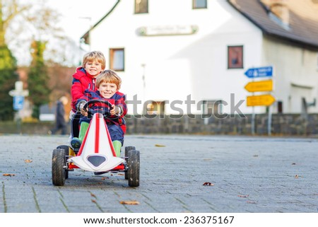 Two little friends kids in red jackets driving fast race car together, outdoors. child leisure on cold day in winter, autumn or spring. Selective focus. - stock photo