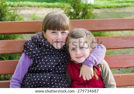 Two little funny girls cuddling sitting on a park bench - stock photo