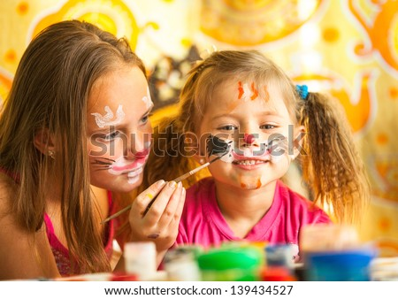 Two little funny sisters playing with painting - stock photo