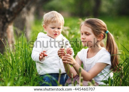 Two little girl blowing dandelions. - stock photo