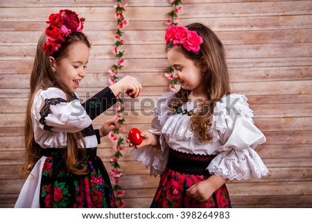 Two little girl in popular Romanian costume enjoying the Easter holidays - stock photo