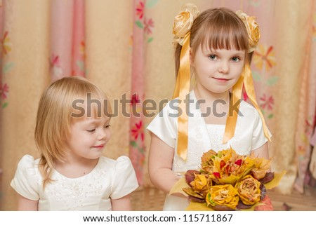Two little girl looks at the bouquet of autumn leaves - stock photo