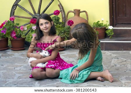 Two little girl with a rabbit.Two little girl with a bunny rabbi - stock photo