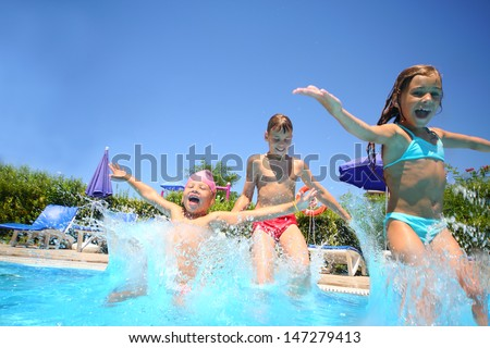Two little girls and boy fun jumping into the swimming pool, shot through the underwater package - stock photo
