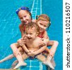two little girls and little boy playing in the pool - stock photo