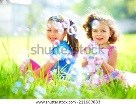 Two little girls are blowing soap bubbles, outdoor shoot - stock photo