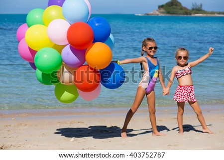 Two little girls are playing and smiling on the beach with colorful balloons - stock photo