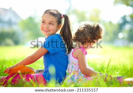 Two little girls are reading books while laying on green grass, outdoor shoot - stock photo