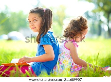 Two little girls are reading books while sitting on green grass, outdoor shoot - stock photo