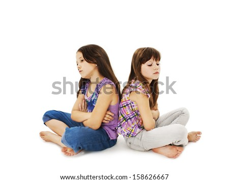 Two little girls back to back in quarrel. Isolated on a white background  - stock photo