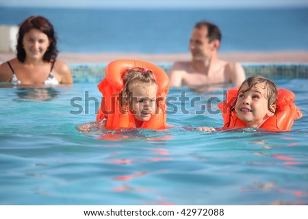 two little girls bathing in life jackets with parents in pool on a resort - stock photo
