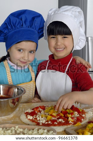 Two Little girls cooking pizza in a kitchen.Little kid in a kitchen together. - stock photo