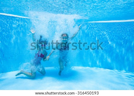 Two little girls deftly swim underwater in pool - stock photo