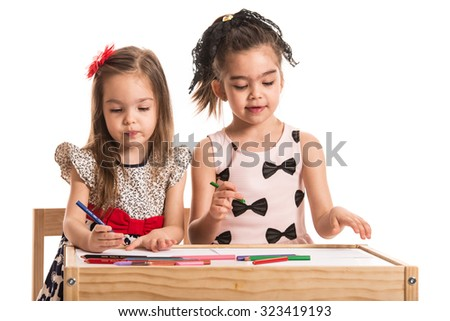 Two little girls drawing on papers at table against white background - stock photo