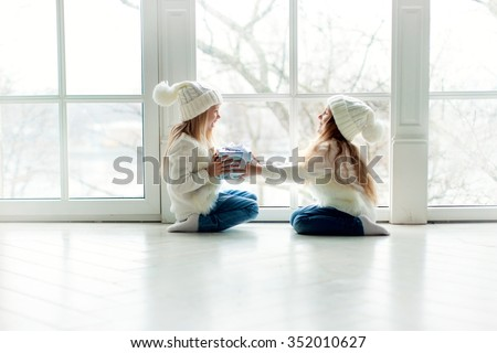 two little girls friends or sisters with long blond hair in white hats and white cardigans and jeans sitting near the window and playing with gift at winter time at winter time - stock photo