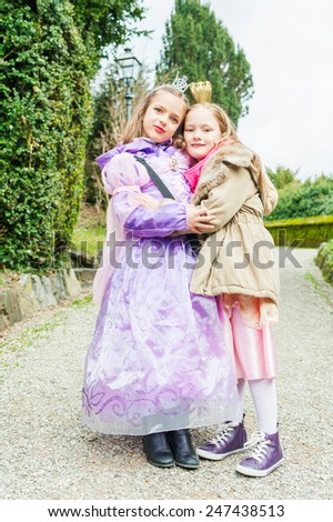 Two little girls friends playing in a park, wearing princess dresses - stock photo