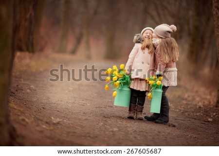 two little girls friends with long blond hair in coats and hats with two green cans with yellow flowers tulips are standing on the road in the park or forest and laughing - stock photo