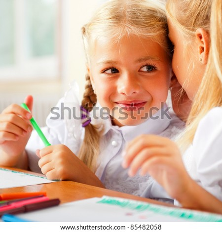 Two little girls gossip in classroom - stock photo