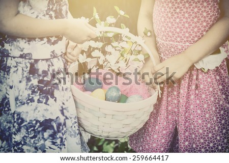 Two little girls hands holding an Easter basket with a eggs and flowers in the spring season.   Part of a series.  Filtered for a retro, vintage look. - stock photo