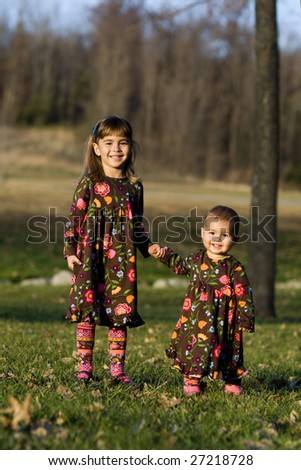 Two little girls holding hands at the park - stock photo