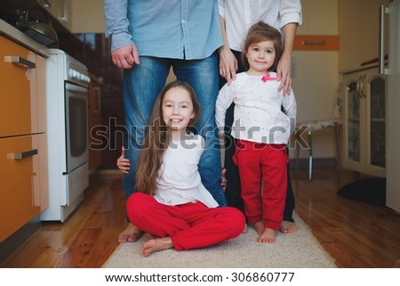 two little girls hugging mom and dad for legs - stock photo