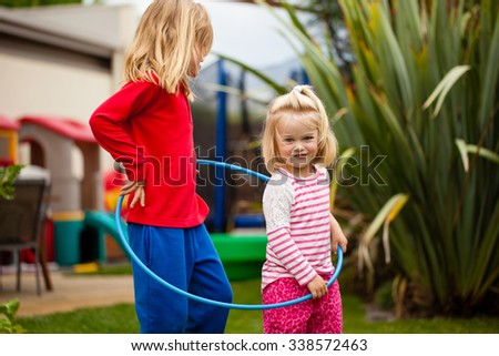 Two little girls in a hula hoop - stock photo