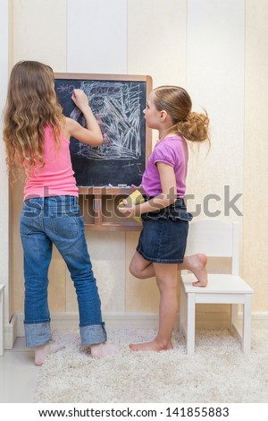 Two little girls in the playroom paint on the blackboard - stock photo