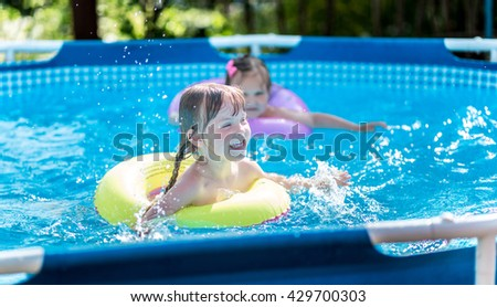 Two little girls in the pool - stock photo
