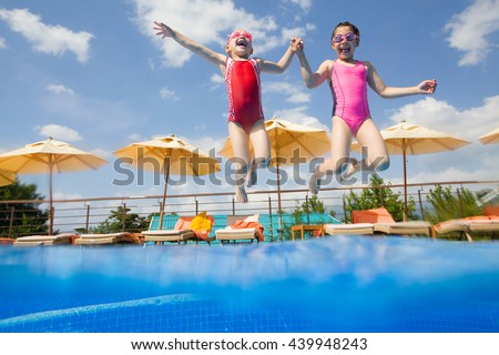 Two little girls jumping in the pool - stock photo