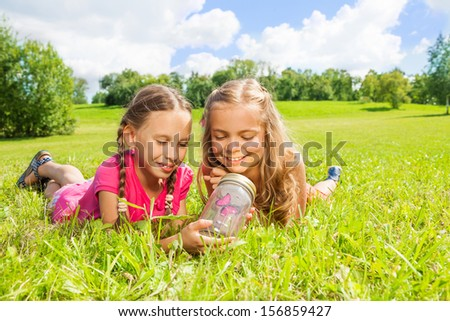 Two little girls lay in the grass looking at the red butterfly in the glass jar - stock photo