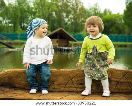 two little girls on the wooden bench in park - stock photo