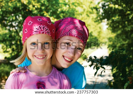 two little girls outdoors with kerchiefs on their heads - stock photo